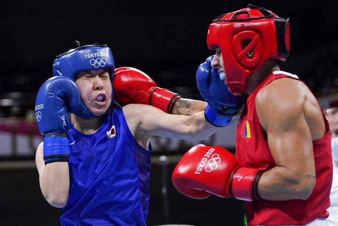 Japan's Sena Irie, left, punches Romania's Maria Nechita during their women's featherweight 57-kg boxing match at the 2020 Summer Olympics, Wednesday, July 28, 2021, in Tokyo, Japan. (AP Photo/Frank Franklin II, Pool)