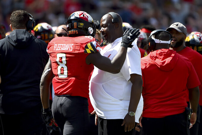 FILE - In this Sept. 7, 2019, file photo, Maryland running back Tayon Fleet-Davis (8) celebrates with head coach Michael Locksley after scoring a touchdown against Syracuse during the second half of an NCAA college football game in College Park, Md. Fleet-Davis and Jake Funk will likely receive the brunt of the carries, at least at the season's outset. Fleet-Davis, a senior, has 589 yards in offense and 10 touchdowns. Funk has 31 games of experience despite missing the final nine games in 2019 with a knee injury. Moreover, as Locksley enters his second season as the helm, he deals with quarterback Josh Jackson opting out of the 2020 season because of the COVID-19 pandemic and Tyrrell Pigrome has transferred to Western Kentucky. Alabama transfer Taulia Tagovailoa and redshirt freshman Lance Legendre have been competing for the starting spot this fall. (AP Photo/Will Newton, File)