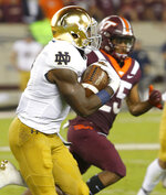 Notre Dame running back Dexter Williams (2) tries to get past Virginia Tech's Khalil Ladler, right, during the first half of an NCAA college football game in Blacksburg, Va., Saturday, Oct. 6, 2018. (AP Photo/Steve Helber)