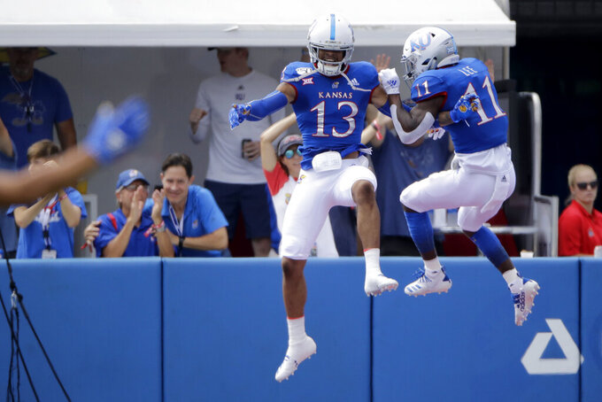 Kansas cornerback Hasan Defense (13) and safety Mike Lee (11) celebrate after Defense returned an interception for a touchdown during the first half of an NCAA college football game against Indiana State, Saturday, Aug. 31, 2019, in Lawrence, Kan. (AP Photo/Charlie Riedel)