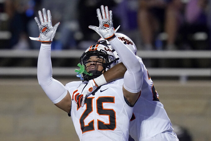 Oklahoma State safety Jason Taylor II (25) celebrates his touchdown with teammate Jarrick Bernard-Converse, back, during the second half of an NCAA college football game against Kansas State in Manhattan, Kan., Saturday, Nov. 7, 2020. Taylor returned a recovered fumble 85 yards. (AP Photo/Orlin Wagner)