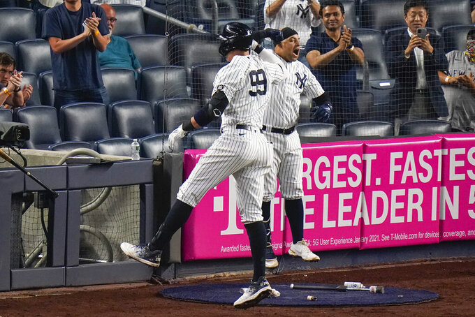 New York Yankees' Aaron Judge (99) celebrates with teammate Rougned Odor after hitting a home run during the sixth inning of a baseball game against the Boston Red Sox, Friday, June 4, 2021, in New York. (AP Photo/Frank Franklin II)