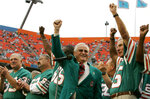 FILE - In this Dec. 16, 2007, file photo, former Miami Dolphins coach Don Shula, center, waves with former players from the 1972 unbeaten team during a ceremony at an NFL football game at Dolphin Stadium in Miami From left are running back Larry Csonka (39), center Jim Langer (62) and linebacker Nick Buoniconti, right. Pro Football Hall of Fame center Jim Langer, who was literally in the middle of the Miami Dolphins' 1972 perfect season, has died at the age of 71. Langer died Thursday, Aug. 29, 2019, at a Coon Rapids, Minnesota hospital near his home of a sudden heart-related problem, said his wife, Linda.(AP Photo/Lynne Sladky)