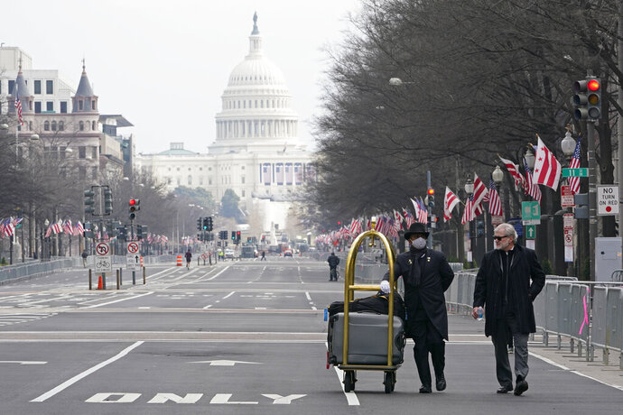 Danish Rozario, left, of Silver Spring, Md., wheels baggage down Pennsylvania Avenue for a guest at the Trump Hotel in Washington, Friday, Jan. 15, 2021, ahead of the inauguration of Joe Biden. (AP Photo/Susan Walsh)