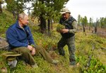 In this undated photo released by Russian Presidential Press Service, Russian President Vladimir Putin, left, talks with Russian Defense Minister Sergei Shoigu in Siberia during a break from state affairs ahead of his birthday. Russian president chose the Siberian taiga forest to go on a hike ahead of his birthday on Oct. 7. (Alexei Druzhinin, Sputnik, Kremlin Pool Photo via AP)