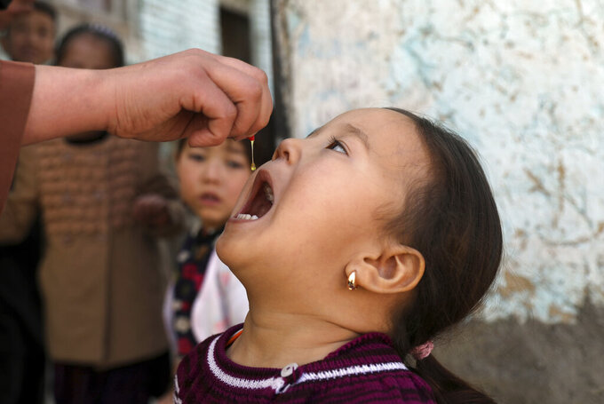 Shabana Maani, gives a polio vaccination to a child in the old part of Kabul, Afghanistan, Monday, March 29, 2021. Afghanistan is inoculating millions of children against polio after pandemic lockdowns stalled the effort to eradicate the crippling disease. But the recent killing of three vaccinators points to the dangers facing the campaign. (AP Photo/Rahmat Gul)