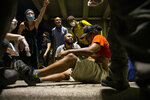 People help a protester after he was shot with a rubber bullet under Interstate 35 freeway in Austin, Texas, Saturday, May 30, 2020, during a protest over the Memorial Day death of George Floyd while in police custody in Minneapolis. (Ricardo B. Brazziell/Austin American-Statesman via AP)