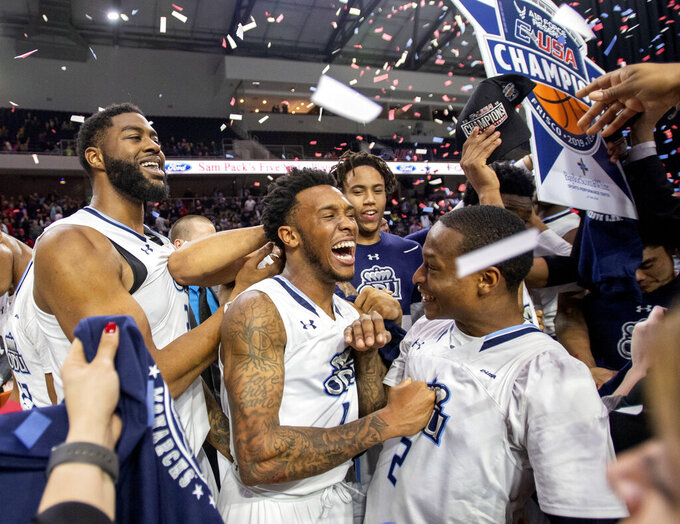 Old Dominion's Ahmad Caver, center, Justice Kithcart (2) and Elbert Robinson III, left, celebrate after Old Dominion defeated Western Kentucky 62-56 in an NCAA college basketball game for the Conference USA men's tournament championship Saturday, March 16, 2019, in Frisco, Texas. (AP Photo/Jeffrey McWhorter)