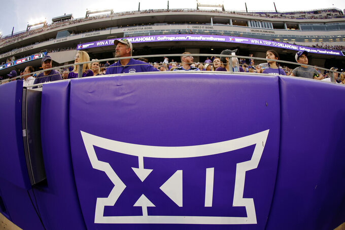 FILE - In this Saturday, Sept. 4, 2021, file photo, a Big 12 Conference logo is displayed on a barrier at Amon G. Carter Stadium before Duquesne played TCU in an NCAA college football game in Fort Worth, Texas. The Big 12 has extended membership invitations to BYU, UCF, Cincinnati and Houston to join the Power Five league. That comes in advance of the league losing Oklahoma and Texas to the Southeastern Conference.  (AP Photo/Ron Jenkins, File)