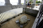 Visitors stand in a pavilion that shelters Plymouth Rock, below, in Plymouth, Mass., Wednesday, June 9, 2021. Archaeologists are excavating the grassy hilltop that overlooks iconic Plymouth Rock one last time before a historical park is built on the site. (AP Photo/Steven Senne)