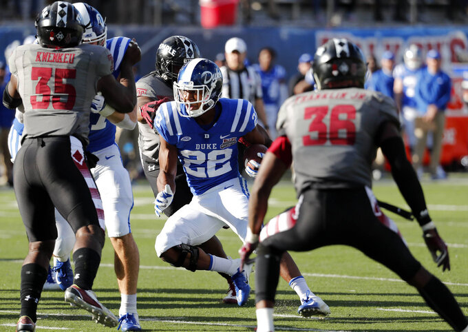 Duke running back Brittain Brown (22) finds running room as he pursued by Temple linebackers William Kwenkeu (35) and Sam Franklin (36) in the second half of the Independence Bowl NCAA college football game in Shreveport, La., Thursday, Dec. 27, 2018. (AP Photo/Rogelio V. Solis)