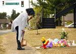 Lynda Menefee, of Fort Worth, makes the sign of the cross after leaving flowers on the front sidewalk of Atatiana Jefferson's home on E. Allen Ave in Fort Worth, Texas, Tuesday, Oct. 15, 2019. Jefferson, a black woman, was shot by a white police officer early Saturday, Oct. 12. (Tom Fox/The Dallas Morning News via AP)