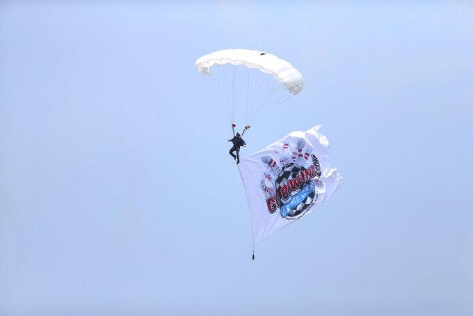 A parachuter helps display at Watkins Glen International flag during a NASCAR Cup Series auto race in Watkins Glen, N.Y., on Sunday, Aug. 8, 2021. (AP Photo/Joshua Bessex)