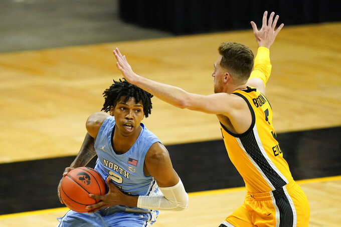 North Carolina guard Caleb Love drives past Iowa guard Jordan Bohannon, right, during the first half of an NCAA college basketball game, Tuesday, Dec. 8, 2020, in Iowa City, Iowa. (AP Photo/Charlie Neibergall)