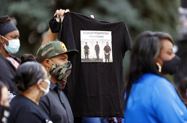A supporter holds up a shirt to call attention to the death of Elijah McClain in August 2019 in Aurora, Colo., during a news conference on the west steps of the State Capitol after Colorado Governor Jared Polis signed a broad police accountability bill Friday, June 19, 2020, in downtown Denver. (AP Photo/David Zalubowski)