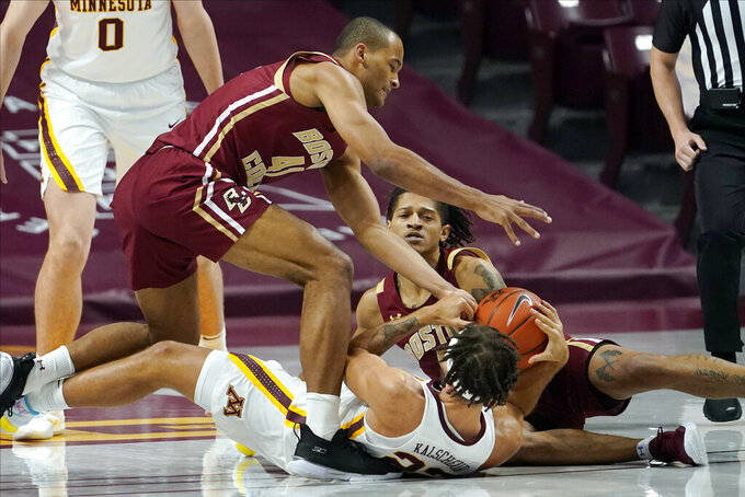 Boston College's Steffon Mitchell, left, and Makai Ashton-Langford scramble for the ball with Minnesota's Gabe Kalscheur, bottom center, during the first half of an NCAA college basketball game Tuesday, Dec. 8, 2020, in Minneapolis. (AP Photo/Jim Mone)