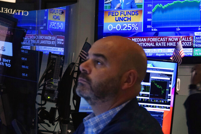 A screen on the floor of the New York Stock Exchange, behind trader Fred Demarco, shows the rate decision of the Federal Reserve, Wednesday, Sept. 22, 2021. The Federal Reserve signaled Wednesday that it may start raising its benchmark interest rate sometime next year, earlier than it envisioned three months ago and a sign that it's concerned that high inflation pressures may persist. (AP Photo/Richard Drew)