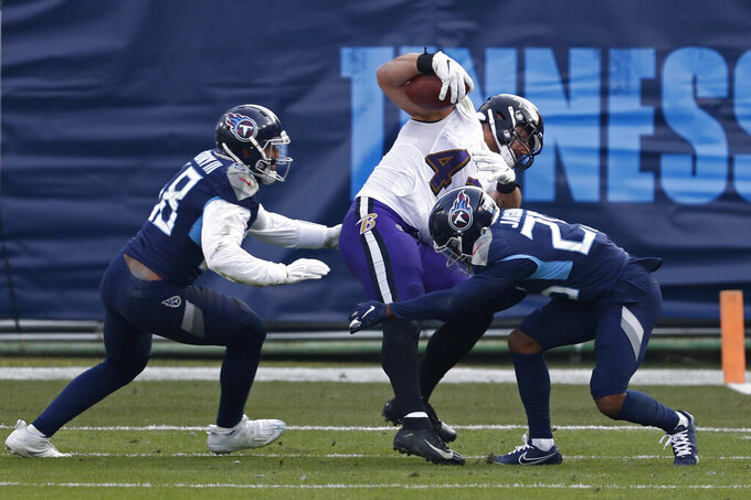 Baltimore Ravens fullback Patrick Ricard (42) is stopped byTennessee Titans defenders Harold Landry (58) and Adoree' Jackson (25) in the second half of an NFL wild-card playoff football game Sunday, Jan. 10, 2021, in Nashville, Tenn. (AP Photo/Wade Payne)