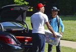 Carolina Panthers wide receiver DJ Moore gets an assist unloading a tub of candy and snacks from his trunk at the team's dormitory at NFL football training camp, Tuesday, July 27, 2021, at Wofford College in Spartanburg, S.C. (Jeff Siner/The Charlotte Observer via AP)