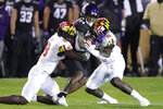 Northwestern wide receiver Malik Washington, center, is tackled by Maryland defensive back Jordan Mosley, left, and linebacker Ayinde Eley during the first half of an NCAA college football game in Evanston, Ill., Saturday, Oct. 24, 2020. (AP Photo/Nam Y. Huh)