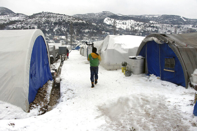 This Thursday, Feb. 13, 2020 photo released by the opposition Syrian Civil Defense rescue group, also known as White Helmets, which has been authenticated based on its contents and other AP reporting, shows Syrian walking outside their tents at a displaced people camp near Turkish border, in Idlib province, Syria. A military offensive on an opposition-controlled region of northwestern Syria has created one of the worst catastrophes for civilians in the country's long-running war, sending hundreds of thousands of people fleeing, many of them sleeping in open fields and under trees in freezing temperatures. (Syrian Civil Defense White Helmets via AP)