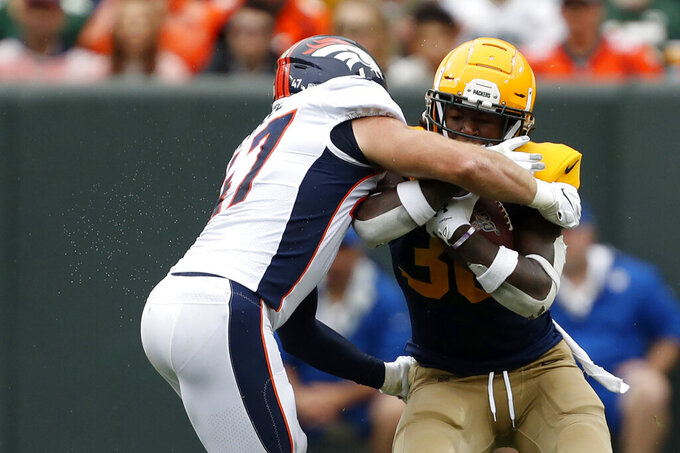 Green Bay Packers running back Jamaal Williams, right, collides with Denver Broncos inside linebacker Josey Jewell while running with the ball during the first half of an NFL football game Sunday, Sept. 22, 2019, in Green Bay, Wis. (AP Photo/Matt Ludtke)