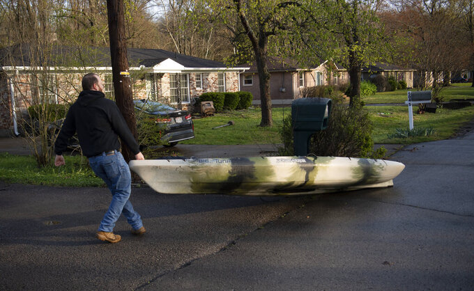 Brian Wolff collects retrieves his kayak from down the street Sunday, March 28, 2021, in Nashville, Tenn. Flash flooding along Sevenmile Creek the night before caused major damage in the South Nashville neighborhood. (George Walker IV/The Tennessean via AP)
