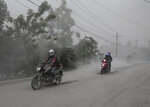Motorcycles ride along an ash covered road as they evacuate to safer grounds as Taal volcano in Lemery, Batangas, southern Philippines on Monday, Jan. 13, 2020. Red-hot lava gushed out of a volcano near the Philippine capital on Monday, as thousands of people fled the area through heavy ash. Experts warned that the eruption could get worse and plans were being made to evacuate hundreds of thousands. (AP Photo/Aaron Favila)
