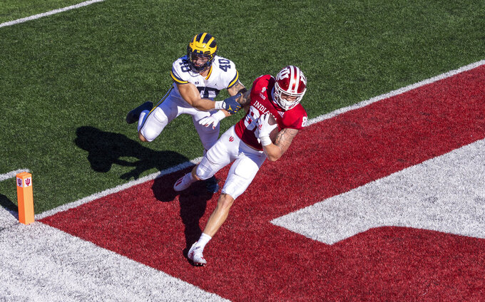 Indiana tight end Peyton Hendershot (86) crosses into the end zone to score ahead of Michigan linebacker Ben VanSumeren (40) during the first half of an NCAA college football game Saturday, Nov. 7, 2020, in Bloomington, Ind. (AP Photo/Doug McSchooler)