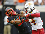 Iowa State wide receiver Tarique Milton (14) fights off a tackle by Oklahoma State cornerback Kris McCune (32) in the second half of an NCAA college football game in Stillwater, Okla., Saturday, Oct. 6, 2018. (AP Photo/Sue Ogrocki)