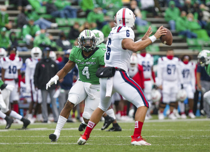 Marshall linebacker Tavante Beckett (4) pressures Florida Atlantic quarterback Nick Tronti (6) as he attempts a pass during an NCAA college football game on Saturday, Oct. 24, 2020, at Joan C. Edwards Stadium Huntington, W.Va. (Sholten Singer/The Herald-Dispatch via AP)