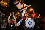 Protesters chant slogans and wave the Israeli national flag during a protest against Israel's Prime Minister Benjamin Netanyahu outside his residence in Jerusalem, Saturday, Oct. 17, 2020. Thousands of Israelis demonstrated outside Netanyahu's official residence for the first time in nearly a month, resuming the weekly protest after emergency restrictions imposed as part of a coronavirus lockdown were lifted. The protesters are demanding Netanyahu's resignation, saying he cannot serve while on trial for corruption charges and accusing him of mismanaging the country's coronavirus crisis. (AP Photo/Ariel Schalit)