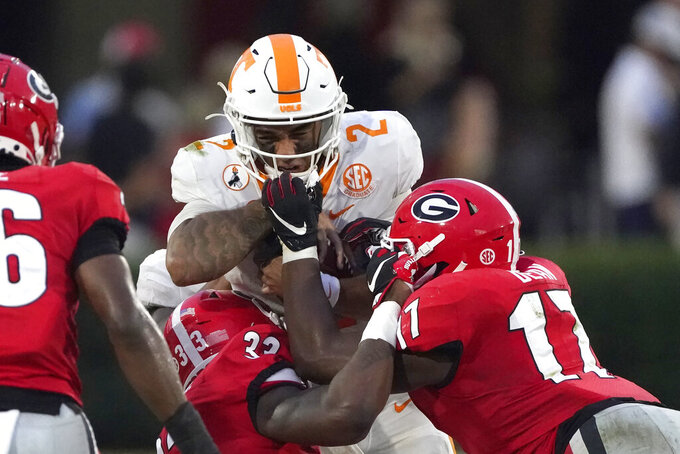 Tennessee quarterback Jarrett Guarantano (2) is stopped short of the first down by Georgia linebackers Monty Rice (32) and Jermaine Johnson (11) in the second half of an NCAA college football game Saturday, Oct. 10, 2020, in Athens, Ga. (AP Photo/John Bazemore)