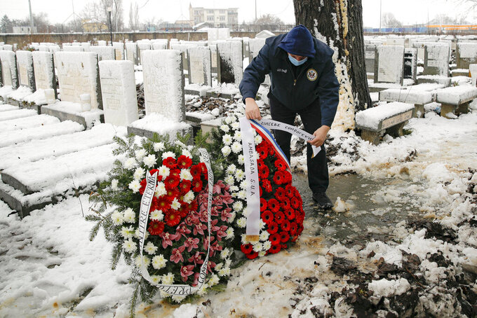 A man adjusts wreaths before the funeral of Iancu Tucarman, at a Jewish cemetery in Bucharest, Romania, Monday, Jan. 11, 2021. Tucarman, one of the last remaining Holocaust survivors in Romania, on was buried after dying from COVID-19 last week at the age of 98. (AP Photo/Vadim Ghirda)