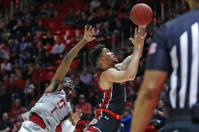 Utah forward Timmy Allen, right, grabs a rebound as Stanford guard Daejon Davis (1) defends in the second half during an NCAA college basketball game Thursday, Feb. 6, 2020, in Salt Lake City. (AP Photo/Rick Bowmer)