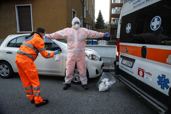 Medical staffer Elisa Bonalumi sanitizes her colleague Ruggero Gariboldi after treating a suspected Covid patient inside the ambulance during their shift with the emergency White Cross in Monza, Italy, Friday, Nov. 20, 2020. The city of Monza north of Milan is best known for its Formula 1 racetrack. In 2020, it has been the ambulance service that has been doing most of the racing. Over three days that an Associated Press photographer traveled on night calls with an ambulance service, the Monza-Brianza province of some 875,000 bordering Milan added 2,500 new cases, part of Italy's new epicenter in the Lombardy region. (AP Photo/Luca Bruno)