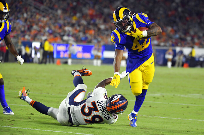 Los Angeles Rams running back John Kelly, right, is tackled by Denver Broncos cornerback Trey Johnson (39) during the second half of an NFL preseason football game Saturday, Aug. 24, 2019, in Los Angeles. (AP Photo/Mark J. Terrill)