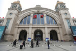 People walk past the closed Hankou Railway Station in Wuhan in central China's Hubei Province, Thursday, Jan. 23, 2020. Overnight, Wuhan authorities announced that the airport and train stations would be closed, and all public transportation suspended by 10 a.m. Friday. Unless they had a special reason, the government said, residents should not leave Wuhan, the sprawling central Chinese city of 11 million that's the epicenter of an epidemic that has infected nearly 600 people. (Chinatopix via AP)