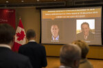 A video screen displays images of Canadians Michael Kovrig, left, and Michael Spavor at an event held in connection with the announcement of the sentence for Spavor at the Canadian Embassy in Beijing, Wednesday, Aug. 11, 2021. A Chinese court has sentenced Spavor to 11 years on spying charges in case linked to Huawei. (AP Photo/Mark Schiefelbein)