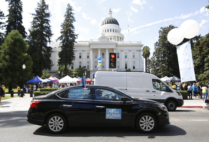 FILE — In this Aug. 28, 2019 file photo supporters of a measure to limit when companies can label workers as independent contractors circle the Capitol during a rally in Sacramento, Calif. U.S. District Judge Dolly Gee denied a request by ride-share company Uber and on-demand a request delivery service Postmates for a preliminary injunction protecting them from the new law aimed at giving protections to people who work as independent contractors, Monday, Feb.10, 2020. (AP Photo/Rich Pedroncelli, File)