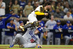 San Diego Padres catcher Victor Caratini leaps over Los Angeles Dodgers' Will Smith after tagging him out during the thirteenth inning of a baseball game Wednesday, Aug. 25, 2021, in San Diego. (AP Photo/Gregory Bull)