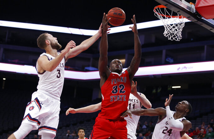 Fresno State forward Nate Grimes, center, goes for the rebound between Saint Mary's Jordan Ford, left, Matthias Tass, back, and Malik Fitts, right, during the second half of an NCAA college basketball game in Sacramento, Calif., Wednesday, Nov. 20, 2019. Saint Mary's won 68-58.(AP Photo/Rich Pedroncelli)