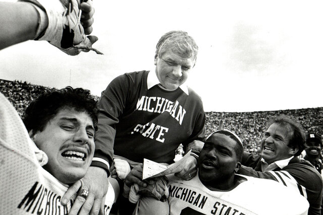 In this 1984 photo, Michigan state NCAA college football head coach George Perles gets lifted on the shoulders of team members after a victory. George Perles, who coached Michigan State to a Rose Bowl victory in 1988 and was an assistant for the dominant Pittsburgh Steelers teams of the 1970s that won four Super Bowls, died Tuesday, Jan. 7, 2020, the school said. He was 85. (Manny Crisostomo/Detroit Free Press via AP)