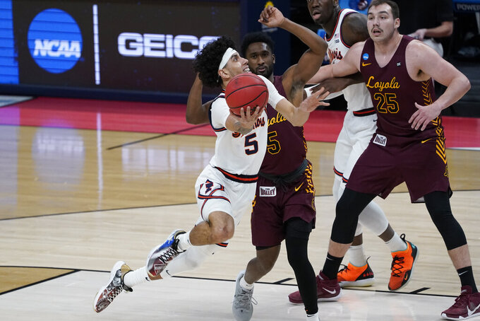 Illinois guard Andre Curbelo (5) drives on Loyola Chicago guard Keith Clemons (5) during the first half of a men's college basketball game in the second round of the NCAA tournament at Bankers Life Fieldhouse in Indianapolis, Sunday, March 21, 2021. (AP Photo/Paul Sancya)