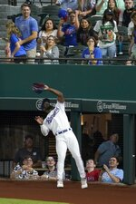 Fans look on as Texas Rangers right fielder Adolis Garcia reaches up to catch a fly ball for the out on Seattle Mariners' Abraham Toro during the fourth inning of a baseball game in Arlington, Texas, Tuesday, Aug. 17, 2021. (AP Photo/Tony Gutierrez)