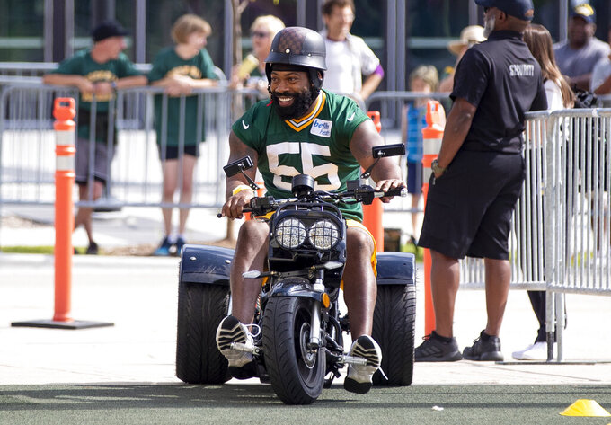 Green Bay Packers Za'Darius Smith (55) arrives to an NFL football training camp practice on a trike scooter at Ray Nitschke Field in Green Bay, Wisc., Monday, Aug. 2, 2021. (Samantha Madar/The Post-Crescent via AP)