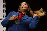 FILE - This Oct. 22, 2019 file photo shows musician and actress Queen Latifah fixing her hair after receiving the W.E.B. Dubois Medal for her contributions to black history and culture during ceremonies at Harvard University in Cambridge, Mass.From Oscar winners to stars on the rise, many African American actresses have similar stories about hair struggles in Hollywood. Queen Latifah said she encountered stylists who didn't know what to do with her hair, particularly early in her career.  (AP Photo/Elise Amendola, File)