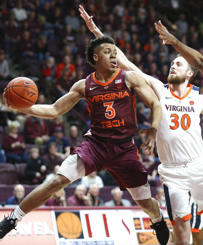 Virginia Tech's Wabissa Bede (3) passes the ball while guarded by Virginia's Jay Huff (30) during the first half of an NCAA college basketball game Wednesday, Feb. 26, 2020, in Blacksburg, Va. (Matt Gentry/The Roanoke Times via AP)