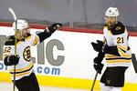 Boston Bruins center Sean Kuraly (52) skates over to congratulate teammate Nick Ritchie (21) after Ritchie scored the Bruins first goal during the second period of an NHL hockey game against the New Jersey Devils, Monday, May 3, 2021, in Newark, N.J. (AP Photo/Kathy Willens)