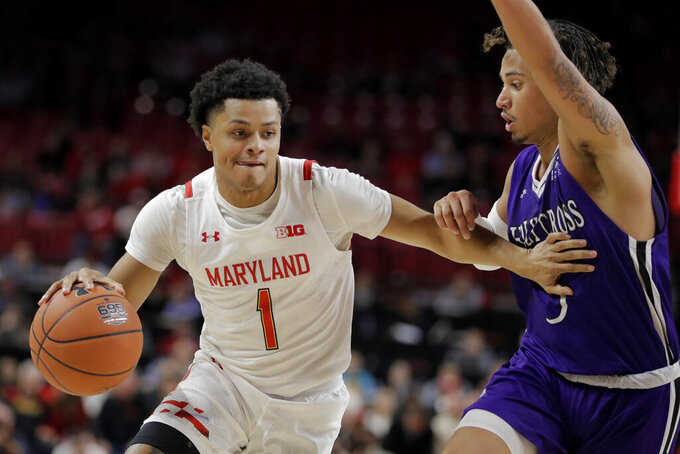Maryland guard Anthony Cowan Jr. (1) drives against Holy Cross guard Drew Lowder (3) during the first half of an NCAA college basketball game, Tuesday, Nov. 5, 2019, in College Park, Md. (AP Photo/Julio Cortez)